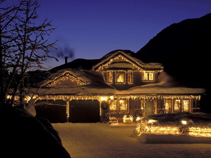 ночной вид дома с гирляндами на новый год