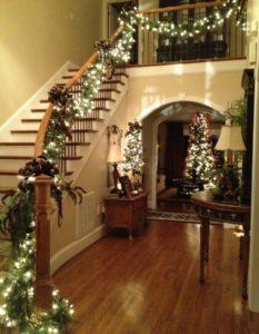 лестница в доме украшенная гирляндами из мишуры