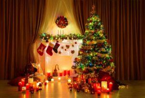 ряд свечей возле камина и елки