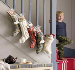 подарочные сапоги на перилах празднично оформленной лестницы