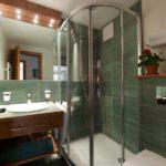 Угловая душевая кабина в интерьере ванной